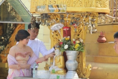 Newlyweds pouring water over their buddha