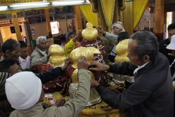 Men putting little pieces of gold leaves on the buddha figures
